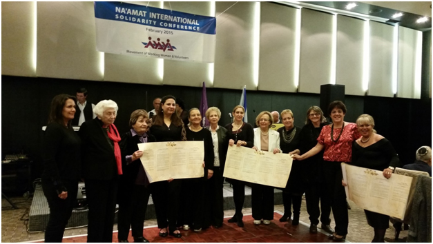 "Past presidents of NA'AMAT Israel Tamar Eshel, Masha Lubelsky, Talia Livni and Ofra Friedman join Galia Wolloch, current president of NA'AMAT Israel, Sarah Beutel, president, Na'amat Canada, and presidents from other Na'amat countries display signed ""Declaration of Solidarity and Support for the State of Israel and Na'amat."""