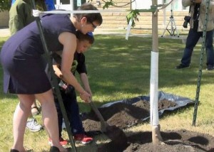 Principal Judith Boyle helps students with the planting.
