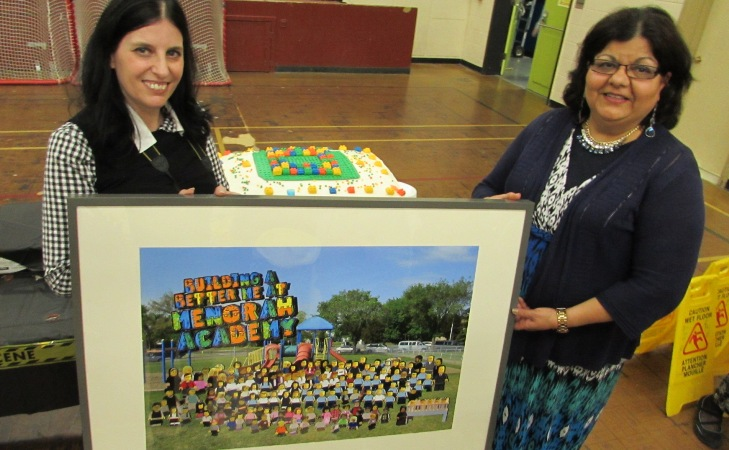 Ms. Scheeler and Mrs. Benjamin admire the  Lego version of the shcool photo with the Lego inspired cake in the background.