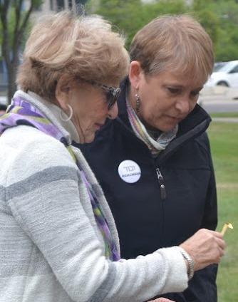Stephanie Hendin and Ann Davis light a candle